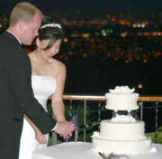 A couple cutting a cake.